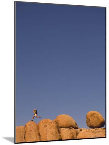 Hiker Jumping on Rocks-Bill Hatcher-Mounted Photographic Print