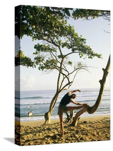 A Woman Stretches Her Body on a Small Tree at a Sandy Beach-Skip Brown-Stretched Canvas Print