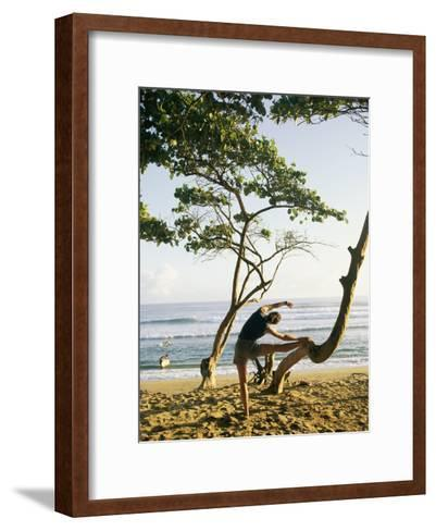 A Woman Stretches Her Body on a Small Tree at a Sandy Beach-Skip Brown-Framed Art Print