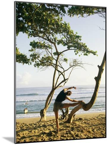 A Woman Stretches Her Body on a Small Tree at a Sandy Beach-Skip Brown-Mounted Photographic Print