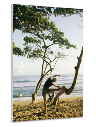 A Woman Stretches Her Body on a Small Tree at a Sandy Beach-Skip Brown-Metal Print