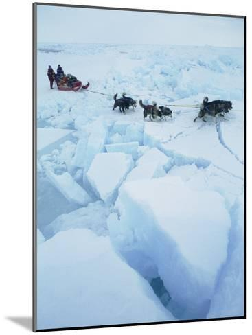 Huskies Carry a Sled Across Broken Ice During an Expedition Traversing the North Pole-Gordon Wiltsie-Mounted Photographic Print