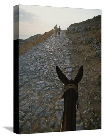 A Couple and a Donkey Walk up the Cobblestone Road to the Acropolis-Tino Soriano-Stretched Canvas Print