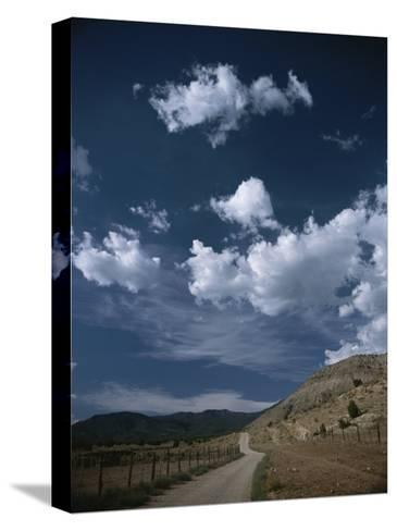 Dirt Road to Ranch Through Desert Hills against a Blue Cloudy Sky-Todd Gipstein-Stretched Canvas Print