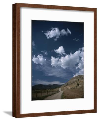 Dirt Road to Ranch Through Desert Hills against a Blue Cloudy Sky-Todd Gipstein-Framed Art Print