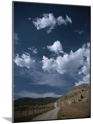 Dirt Road to Ranch Through Desert Hills against a Blue Cloudy Sky-Todd Gipstein-Mounted Photographic Print