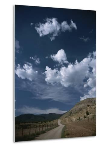 Dirt Road to Ranch Through Desert Hills against a Blue Cloudy Sky-Todd Gipstein-Metal Print