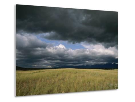 Dark Clouds Gather over a Prairie in the National Bison Range-Annie Griffiths Belt-Metal Print