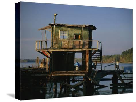 A Man Sits on a Pier Near a Dilapidated Shack-Raymond Gehman-Stretched Canvas Print