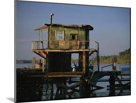 A Man Sits on a Pier Near a Dilapidated Shack-Raymond Gehman-Mounted Photographic Print