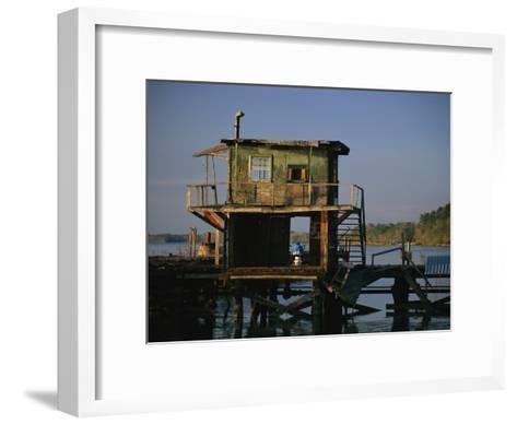 A Man Sits on a Pier Near a Dilapidated Shack-Raymond Gehman-Framed Art Print