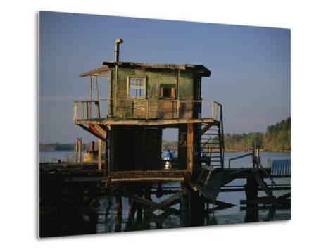 A Man Sits on a Pier Near a Dilapidated Shack-Raymond Gehman-Metal Print