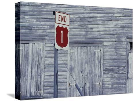 An Old Barn of Weathered Wood and a Road Sign-Medford Taylor-Stretched Canvas Print