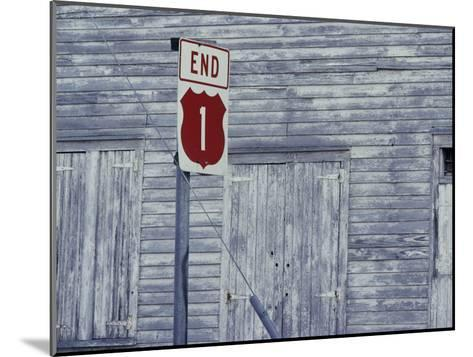 An Old Barn of Weathered Wood and a Road Sign-Medford Taylor-Mounted Photographic Print