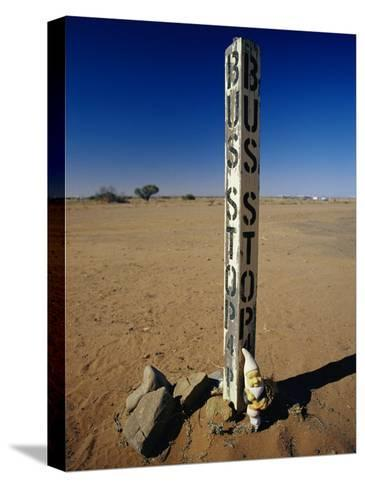 A Garden Gnome at a Bus Stop in an Outback Desert Town-Jason Edwards-Stretched Canvas Print