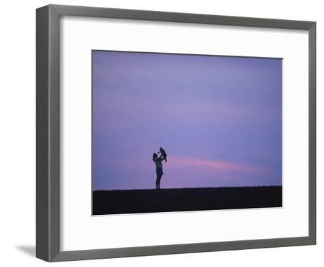 A Mother Holding up Her Baby Sihouetted against a Sky at Sunset-Joel Sartore-Framed Art Print