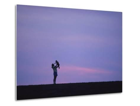 A Mother Holding up Her Baby Sihouetted against a Sky at Sunset-Joel Sartore-Metal Print