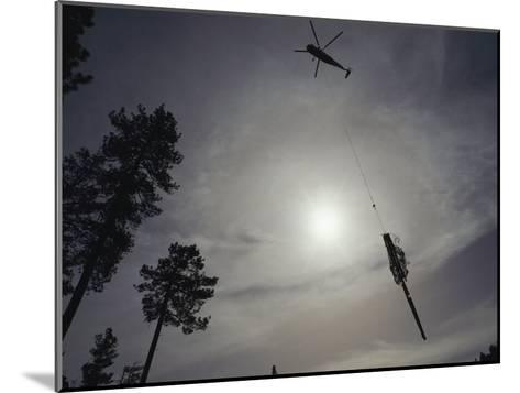 A Helicopter Lifts Cut Timber from the Forest; Helicopter Logging is Said to be Easier on Forest-Joel Sartore-Mounted Photographic Print