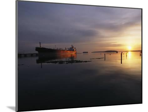 Twilight View of a Ship at Anchor in Still Water at Low Tide-Bill Curtsinger-Mounted Photographic Print