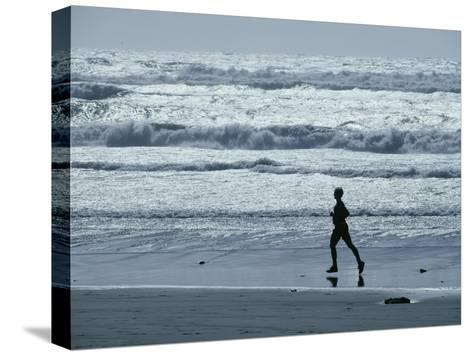 A Person Jogs Along the Beach-David Boyer-Stretched Canvas Print