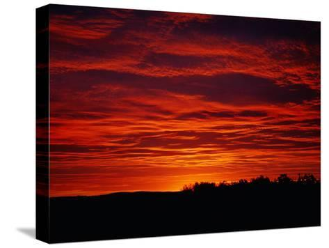 A Sunrise Bathes the Clouds in a Red Glow-Heather Perry-Stretched Canvas Print