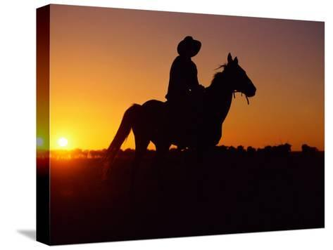A Cowboy and His Horse Ride off in to the Sunset-Medford Taylor-Stretched Canvas Print