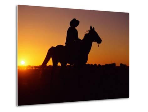 A Cowboy and His Horse Ride off in to the Sunset-Medford Taylor-Metal Print