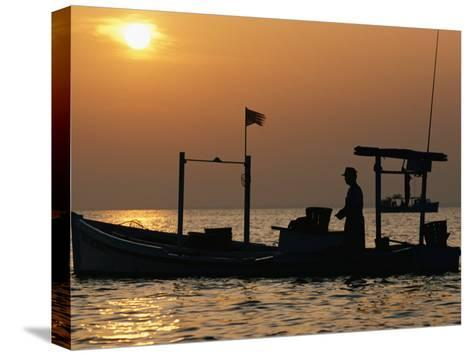A Silhouetted Boat Fishing for Soft Crabs-Robert Madden-Stretched Canvas Print