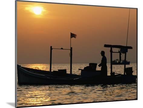 A Silhouetted Boat Fishing for Soft Crabs-Robert Madden-Mounted Photographic Print