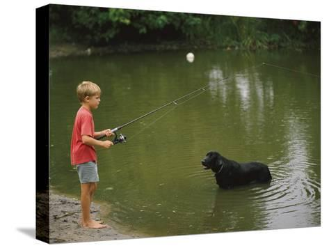 Boy Fishing in a Pond with a Black Labrador Retriever Standing in the Water-Brian Gordon Green-Stretched Canvas Print