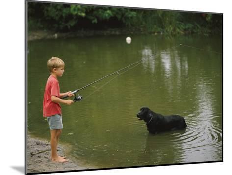Boy Fishing in a Pond with a Black Labrador Retriever Standing in the Water-Brian Gordon Green-Mounted Photographic Print