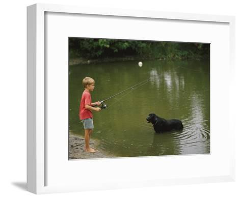 Boy Fishing in a Pond with a Black Labrador Retriever Standing in the Water-Brian Gordon Green-Framed Art Print