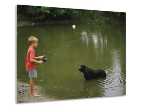 Boy Fishing in a Pond with a Black Labrador Retriever Standing in the Water-Brian Gordon Green-Metal Print