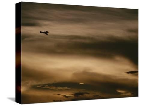 A Small Airplane Flies Through a Cloudy Sky over Key West, Florida-Raul Touzon-Stretched Canvas Print