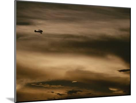 A Small Airplane Flies Through a Cloudy Sky over Key West, Florida-Raul Touzon-Mounted Photographic Print