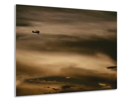 A Small Airplane Flies Through a Cloudy Sky over Key West, Florida-Raul Touzon-Metal Print