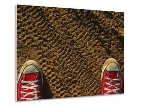 Red Sneakers on Soil Patterned with Tire Tracks-Joel Sartore-Metal Print