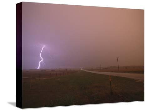 Cloud-To-Ground Lightning Strikes a Field and Brightens a Foggy Sky-Peter Carsten-Stretched Canvas Print