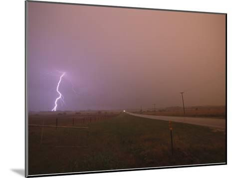 Cloud-To-Ground Lightning Strikes a Field and Brightens a Foggy Sky-Peter Carsten-Mounted Photographic Print