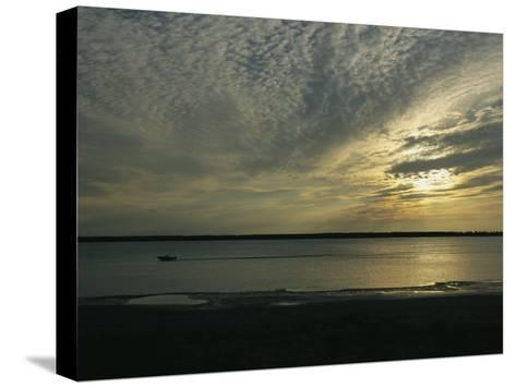 A Boat Speeds Past the Shoreline of the Mackenzie River at Sunset-Raymond Gehman-Stretched Canvas Print