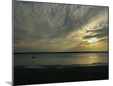 A Boat Speeds Past the Shoreline of the Mackenzie River at Sunset-Raymond Gehman-Mounted Photographic Print