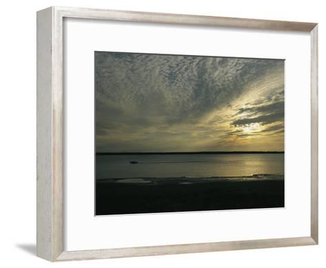A Boat Speeds Past the Shoreline of the Mackenzie River at Sunset-Raymond Gehman-Framed Art Print