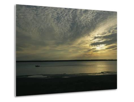 A Boat Speeds Past the Shoreline of the Mackenzie River at Sunset-Raymond Gehman-Metal Print