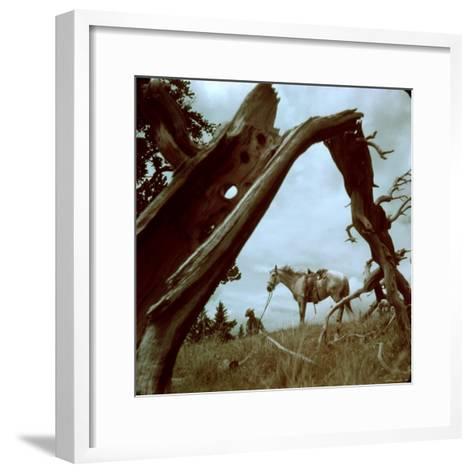 Rancher Leading Horse Across Field as Seen Through Branches of Fallen Tree, Trinchera Ranch-Loomis Dean-Framed Art Print