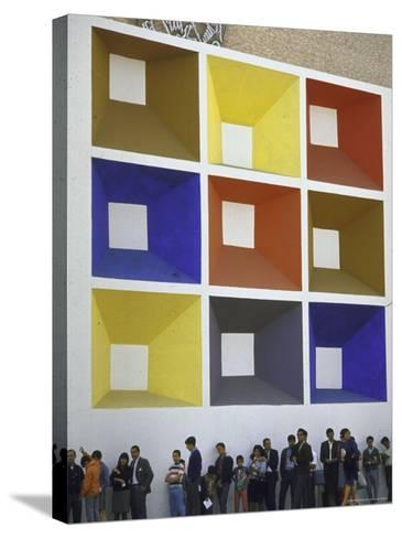 Line of People under Building Facade Painted with Brightly Colored Geometric Pattern-John Dominis-Stretched Canvas Print