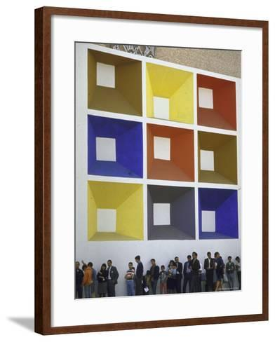 Line of People under Building Facade Painted with Brightly Colored Geometric Pattern-John Dominis-Framed Art Print