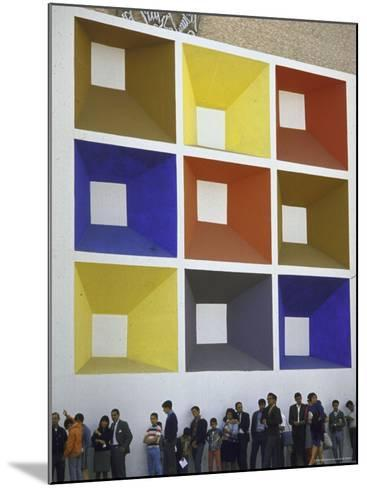 Line of People under Building Facade Painted with Brightly Colored Geometric Pattern-John Dominis-Mounted Photographic Print