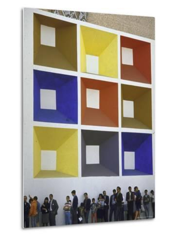 Line of People under Building Facade Painted with Brightly Colored Geometric Pattern-John Dominis-Metal Print