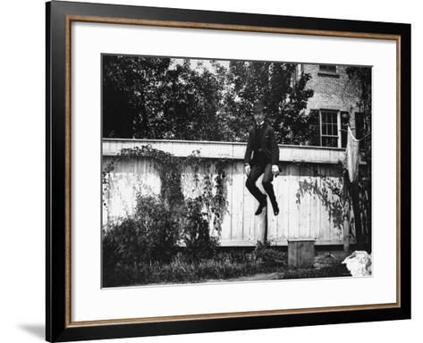 Man in a Suit and Bowler Hat Jumping in the Air in a Backyard in Brooklyn, Ny-Wallace G^ Levison-Framed Art Print