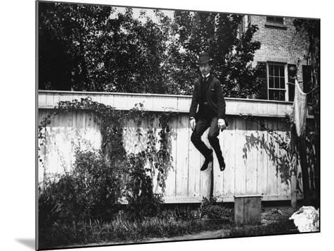 Man in a Suit and Bowler Hat Jumping in the Air in a Backyard in Brooklyn, Ny-Wallace G^ Levison-Mounted Photographic Print